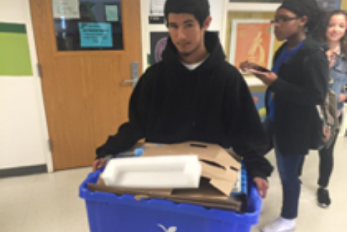 high school student carrying a compost bin to class