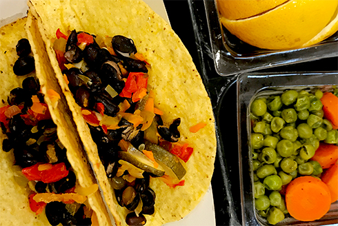 Black bean and veggie tacos with a side of peas and carrots with sliced orange