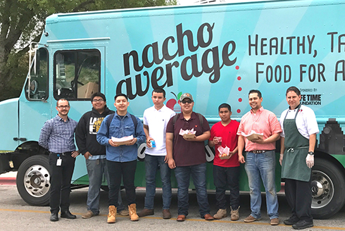 Group of highschool students standing in front of the Nacho Average food truck holding food