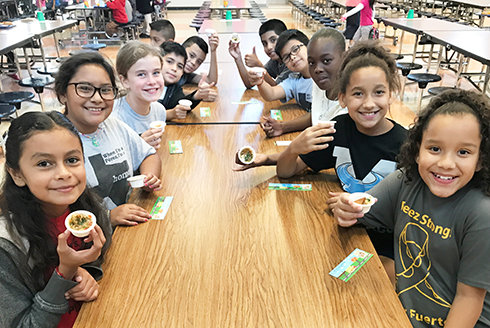 Ten elementary school students in cafeteria sampling baba ganoush