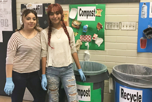 high school students standing by compost bins in hallway