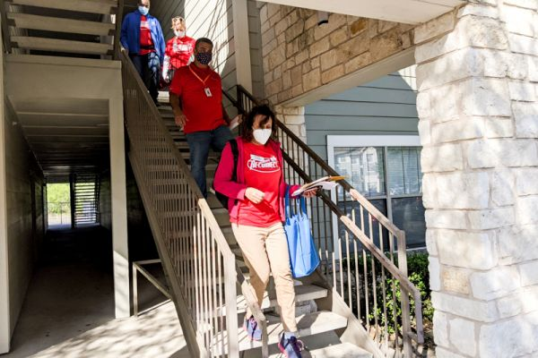 Four AISD Operation Reconnect volunteers walk down apartment complex stairs